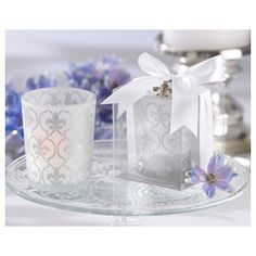 Long a distinctive symbol of royalty, the lovely fleur-de-lis graces this gorgeous frosted-glass tea light holder—creating warmth and bright memories for your guests. Magnificent detail is the hallmark of this exquisite favor, from the intricate pattern on the tea light holder to the delicate, silver-finish fleur-de-lis charm included in the gift presentation.