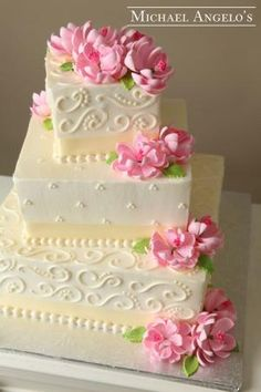 Gorgeous square tiered cake iced and decorated in buttercream, with gumpaste flowers. by Epiphany