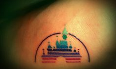 """Disney logo tattoo (Perhaps change color scheme to Tangled (Blonde, light pink, purple, teal, brown), and add Disney """"D"""" in black in center). Between shoulder blades."""
