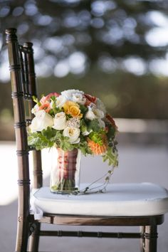 October bridal bouquet in ivory, white, coral, orange and peach. Flowers used are: garden roses, dahlias, ranunculus, geranium foliage, string of hearts, parrot tulips, riceflower. By Fleurie