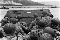 Cette photo, prise le 6 juin 1944, montre des soldats américains à bord d'une barge (une énorme barque plate et large) sur le point de débarquer sur une plage de Normandie. Au second plan, tu peux voir de la fumée : elle a été provoquée par un bombardement. (© Photo AFP)