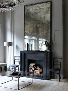 Espejo antiguo sobre chimenea en desuso