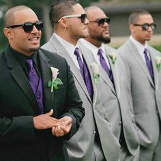 Groom black on black w/ purp accents, groomsmen gray tuxs with white shirt and matching purple accents. Purple socks too!