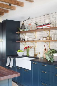 monochromatic blue cabinets + dark counters. white subway tile, wood shelves, brass brackets and brass hardware. YES.