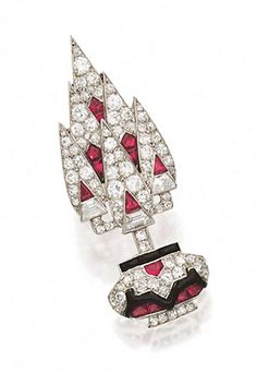 DIAMOND, RUBY AND ONYX BROOCH, FRENCH, CIRCA 1920. The stylized topiary motif set with 3 trapezoid-cut diamonds and numerous single-cut diamonds, further accented with calibré-cut rubies and onyxes and decorated with black enamel, mounted in platinum, assay marks.
