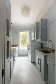 Long gray laundry room boasts a tension rod drying rack mounted to gray shaker cabinets fixed on either side of an undermount sink fitted with a polished nickel pull out faucet framed by a taupe countertop positioned on gray shaker cabinets finished with satin nickel pulls.