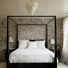 Exposed brick, clean lines canopy bed, contrasting white bedding and feminine chandelier ...lovely
