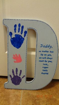 wood 'D' from hobby lobby. painted myself. kids hand prints. used puff paint for little boarder and for writing. tripple gloss coat. gifts for dad from daughter | gifts for dad from kids | gifts for dad from daughter birthday | gifts for dad to be | gifts for father | gifts for father from daughter