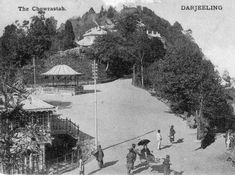 Chowrasta, the square in Darjeeling around 1905. Note the two palanquin bearers carrying a British lady holding a parasol.