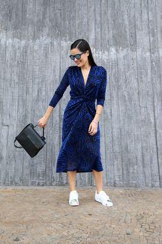 Look de street style com vestido azul marinho e lurex manga longa Carol Bassi Brand e tênis Adidas modelo Super Star, bolsa preta de couro Delvaux.