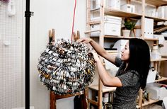 Strips of pages from the IKEA catalog being glued to a rice paper lamp shade
