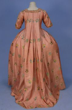 SILK BROCADE ROBE a la FRANCAISE, c. 1750. Red and white striped silk open gown and petticoat brocaded with floral sprays in yellow, blue, plum and green having short sleeve, square neck, front opening flanked by graduated padded furbelows with looped silk cord trim, neckline, faux waistcoat and sleeve similarly trimmed.