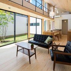 空を囲む家の部屋 中庭を望める勾配天井のLDK
