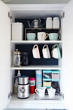 It's amazing what a difference some dark paint makes when trying to find items. Plus, hooks attached to the bottom of a shelf allows mugs to hang, while dividers create shorter shelves for even more coffee cups. See more at I Heart Organizing Coffee Mug Storage, Coffee Cabinet, Coffee Cups, Coffee Nook, Coffee Corner, Coffee Maker, Coffee Latte, Kitchen Cabinet Organization, Organization Hacks