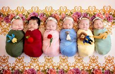 six babies in a line dressed as Disney princesses