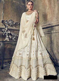 Get this chic cream embroidered lehenga choli in satin with net half sari. This bridal lehenga choli dupatta set has floral embroidery, border & stone work. Lehenga Choli Designs, Ghagra Choli, Lehenga Choli Online, Bridal Lehenga Choli, Pakistani Bridal, Pakistani Dresses, Indian Bridal, Indian Dresses, Wedding Lehnga