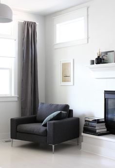 Create a cozy nook with a minimal armchair and throw cushion near a window for natural reading light.