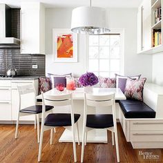 Small dining rooms are often nooks carved out of larger spaces. Unify the dining area with the surrounding spaces by employing similar design characteristics. Just a step away from the kitchen, this nook carries the sleek black-and-white color scheme of the adjacent kitchen, but is distinguished by plum accents. A round light fixture contrasts the square table and cabinets and adds a modern touch with its silver lining inside./