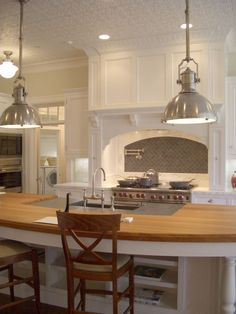 White kitchen cabinets, calcutta marble backsplash & countertops, gray herringbone tiles backsplash, pot filler, kitchen island with butcher block countertops and industrial yoke pendants.
