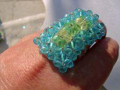Ein toller Ring mit facettierten Glasperlen in Wasserfarben, die hier glitzern und funkeln dürfen.  Ein angenehm tragbarer und doch großer Ring in ...