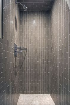 Warm beige tiled shower with varying sizes and patterns including ...