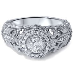 This spectacular engagement ring boasts a vintage style with its round-cut center diamond detailed with filigree accents. Set in 14k white gold with dazzling side stones, this ring shines with a high polish finish.