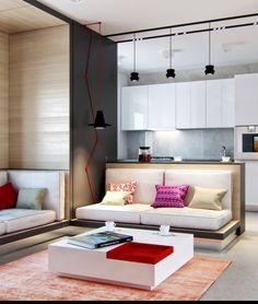 Um apartamento pequeno com ambientes integrados e uma decoração charmosa. A parede cinza deixa em destaque o cabo vermelho, assim como os pendentes pretos.