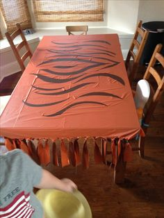 The cloth was made with one orange tablecloth and one black one tied together. The tiger strips where then cut out of the overlapping cloth (orange) to show ...
