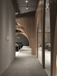 """Wooden partitions with arch-shaped cutouts are used to separate the workspaces from an indoor """"courtyard"""" inside fashion brand H&M'slogistics office in Taiwan. The office on the outskirts of Taipei. Commercial Interior Design, Office Interior Design, Commercial Interiors, Office Interiors, Interior Design Inspiration, Design Ideas, Discount Interior Doors, Grey Interior Doors, Luxury Interior"""