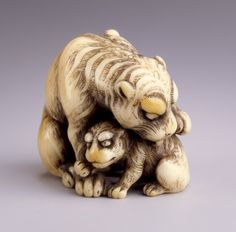 Netsuke. Tiger and Cub. Tomotada (Japan, active before 1781). Japan, 18th century. Ivory with staining, sumi, inlays. LACMA