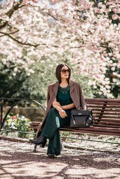 Anisa Sojka styles vintage brown tailored coat   Green crochet top   Khaki green H&M loose wide-leg flared trousers with revealing slit   Black ankle boots   Aubergine Celine cat eye sunglasses   Top handle handbag   Tucked in hair   Fashion blogger street style shot in a cherry blossom tree park on a bench by Mikael Miettinen & Mikaela Watsfeldt