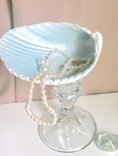 Beautiful way to display and hold jewelry for easy access for beach lovers. Large shell is painted white on the outside and a lovely pearl pale seafoam on the inside ten mounted on a gorgeous sparkly pedestal cut glass stand. Im not sure if this is crystal but its gorgeous. Would be an