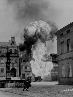 a-lchemist:    Two anti-tank Infantrymen of the 101st Infantry Regiment, dash past a blazing German gasoline trailer in square of Kronach, Germany.  April 14, 1945.