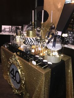 Black, White and Gold Candy Buffet with a Glamorous 2-tier fondant cake brushed with edible gold shimmer. Mirrors, Bling, Satin, all with an Art Deco feel. Black and White photos of European cities along the backsplash. This was an elegant and contemporary affair.