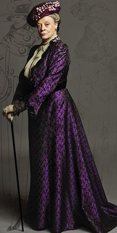 "Lady Violet, the Dowager Countess  ""This outfit was made for Maggie Smith as Violet. The fabric was created by reproducing an Edwardian print onto silk. The design was based on a jacket from the era. We used original lace for the edging and cuff detail. The blouse had a lace bow and high neck added. The hat has vintage cotton baubles covered with a fine net dyed to match the suit.""-- costume designer Susannah Buxton"
