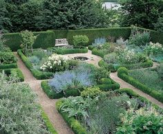 "Landscape architect Charles J. Stick designed an English-style garden at the side of the residence. Pebble paths divide boxwood-lined beds filled with rambling roses, Russian sage, Himalayan musk and other plantings. ""It's a peaceful, fragrant place to rest,"" Buatta says."