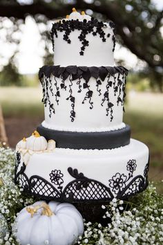 Black lace and white wedding cake with white pumpkin accents | Glamorous Halloween Wedding Inspiration via @BelleMagazine