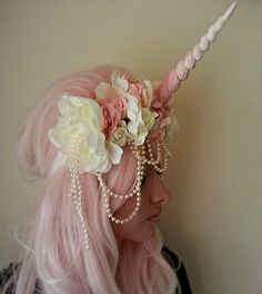 A head dress adorned with a plastic resin unicorn horn and dressed with an assortment of pastel pink and white roses. This head-dress is held in place with a thick elastic.