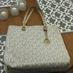 Michael kors large logo tote White large logo tote gently used. I only used this purse for work for one season! Handles gently worn and the inside looks brand new. No scratches or marks on outside of purse. Only marks are on the handles but that is normal with brown leather handles. Marks on handles are not noticeable. Please only serious offers and I do not trade. Michael Kors Bags Totes
