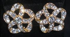 Rhinestone Gold Tone Flower Figural Vintage Clip On Earrings. Rhinestone ornate flower shaped earrings with gold toned outline and backing. Rhinestone single center stone. Clip on backs.