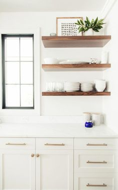 All white kitchen with wood accents, love these floating shelves and the pretty black windows #kitchenshelving