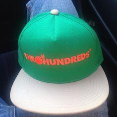 The Hundreds Forever Bar Logo snapback. Green body, Orange logo, Cream colored bill and snap closure.