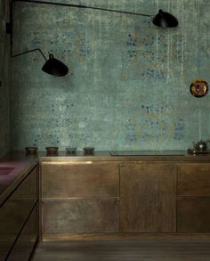 "Brass / metal kitchen cabinets with green ""fresco"" wallpaper and black swing arm pendants"