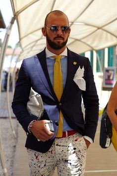 Men's White Pocket Square, Light Blue Long Sleeve Shirt, Yellow Knit Tie, Yellow Lapel Pin, White Leather Zip Pouch, Navy Blazer, Red Leather Belt, and White Print Chinos