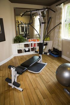 Small home fitness studio with an all-in-one resistance machine, stability ball and mirrors on the wall
