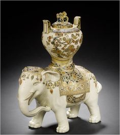 A Satsuma koro and cover in the form of a richly caparisoned elephant By Jukokuzan, Meiji Period  Richly enamelled and gilt, the noble beast striding forward in an elaborate jewelled harness; his back applied with a vase and removable cover, the latter pierced and surmounted with a finial in the form of a recumbent shishi, signed Jukokuzan.