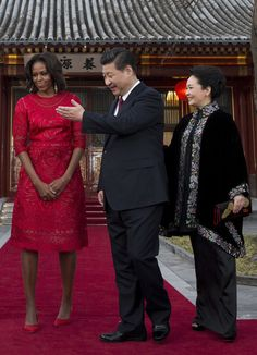 Michelle Obama Photos Photos - Chinese President Xi Jinping and his wife Peng Liyuan (R) show the way to U.S. first lady Michelle Obama after a photograph session at the Diaoyutai State guest house on March 21, 2014 in Beijing, China. Michelle Obama's one-week-long visit in China will be focused on educational and cultural exchanges. - Michelle Obama Travels to China: Day 2