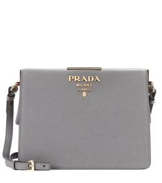 Prada - Exclusive to mytheresa.com – saffiano leather shoulder bag - Prada's exquisite shoulder bag has been crafted in Italy from the label's favoured textured saffiano leather. The boxy silhouette is clean-cut and minimalist, while the brand's iconic logo in gold-tone metal adds glossy recognition. We love this muted grey hue for desk-to-dinner days. seen @ www.mytheresa.com