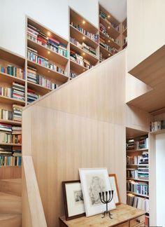 estanterias originales, escalera de madera con librerías iluminadas por luces empotradas, mesita con bocetos y candelabro