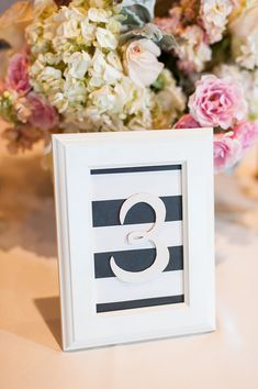 Mount your table numbers onto black and white striped paper in white frames for a clean, modern look! {@candicebenjamin}